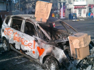 Blockupy-Proteste - Ausgebranntes Polizeiauto von Demonstrierenden kommentiert: Keine Gewalt!